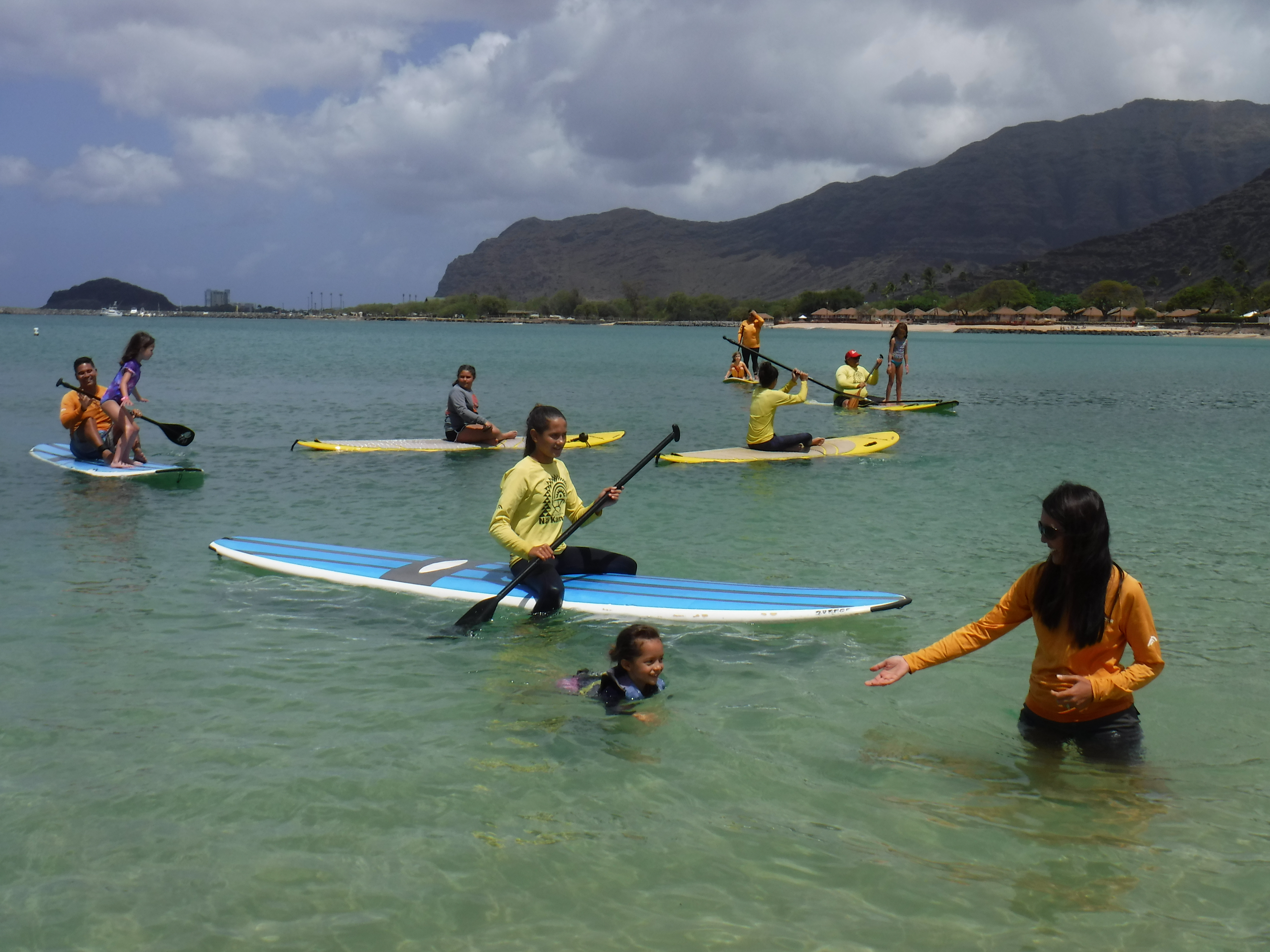 <p>Participants and volunteers paddle their boards back to shore near the end of the clinic.</p>
