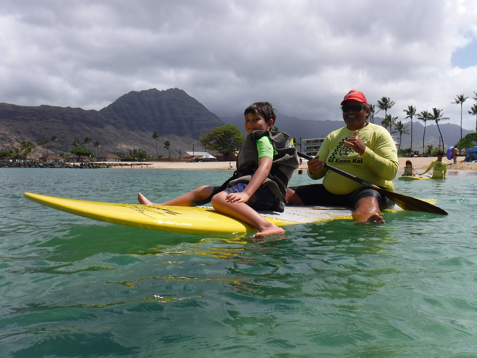 <p>Kaeden Nolasco of Mililani, left, gets paddle board instruction from volunteer Kaipo Sarkissian.</p>