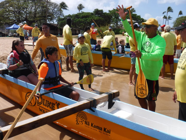 A volunteer instructs kids on how to hold their paddles as they prepare to launch an outrigger canoe into the ocean at the Poka'i Bay Beach Park Saturday, April 14, 2019. Children are taught three main concepts based on the acronym, KAI: Know your limits, Ask a lifeguard, and Identify hazards, so they will learn to enjoy ocean activities safely. (CivilBeat photo Ronen Zilberman)