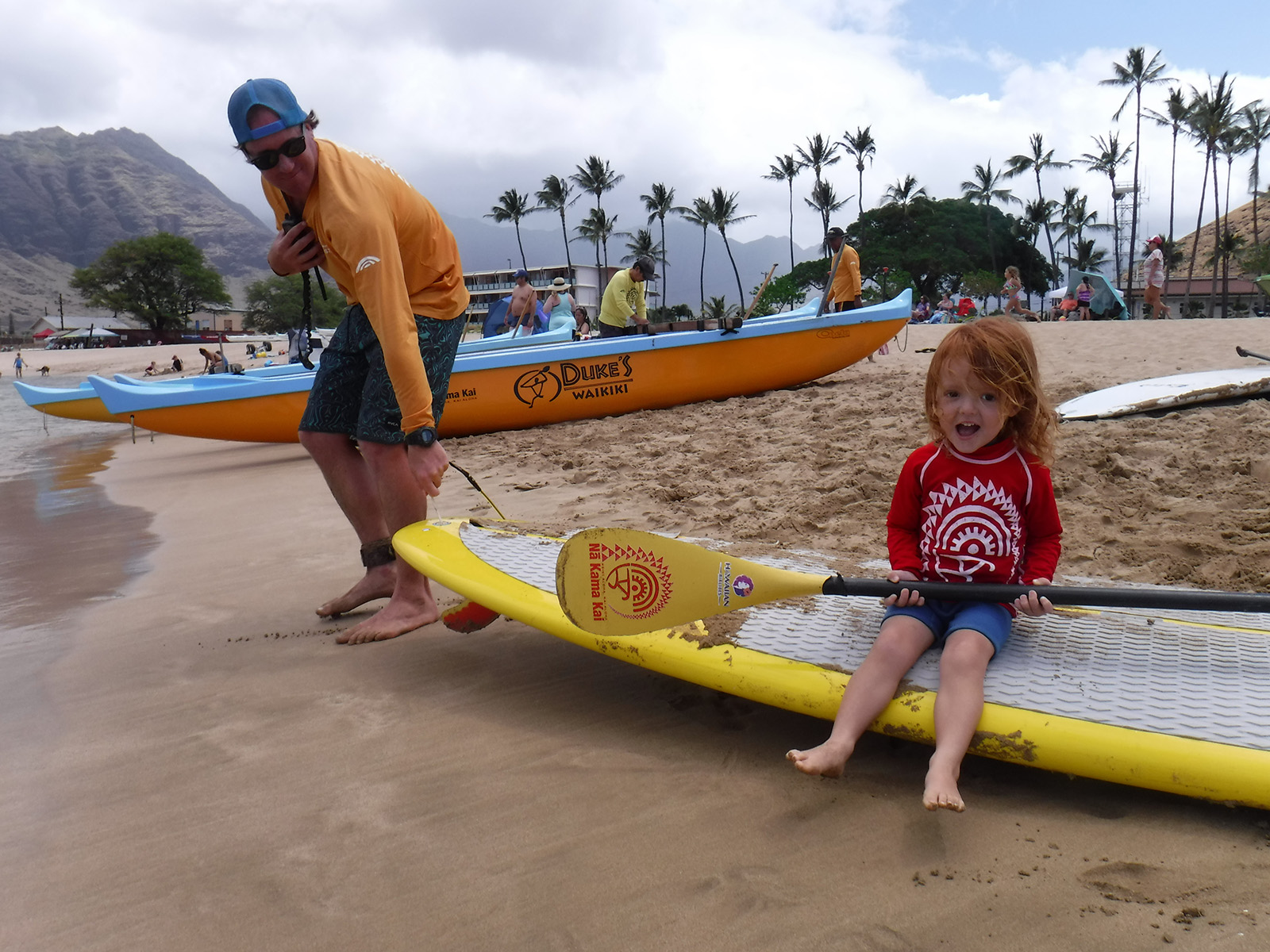 <p>Anthony Aurely and his son, Laiku, prepare to take a paddle board into the water during the Na Kama Kai ocean clinic.</p>