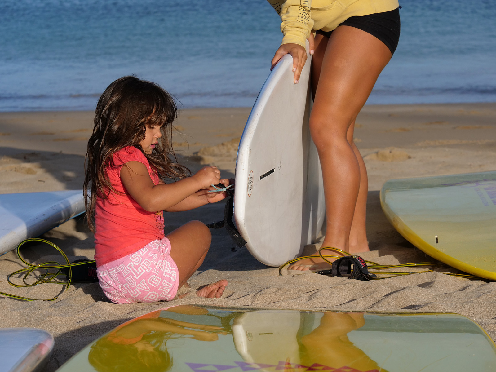 <p>Papua DeSoto, 5, attaches a fin to a paddle board in preparation for the ocean clinic. The clinics are held monthly around Oahu to teach safety and stewardship to young people ages 2-18.</p>
