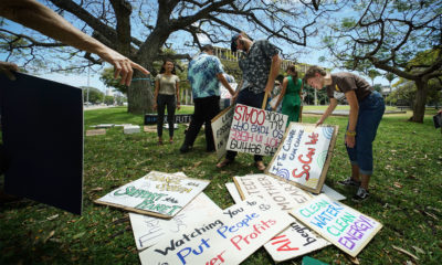 Demonstrators sort thru some signs before the speakers on lawn of the Capitol. According to demonstrators, over 70 climate related bills died.