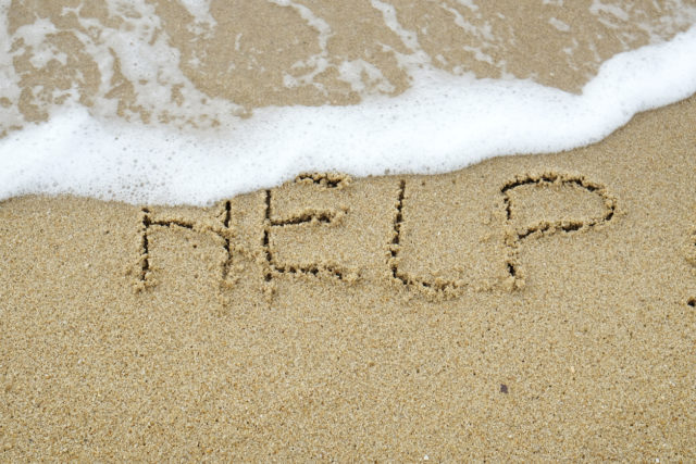 The word HELP written on sand being washed away by wave