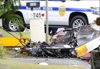 The wreckage of a helicopter lies on the street after crashing in Kailua, Hawaii, Monday, April 29, 2019. Fire and helicopter parts rained from the sky Monday in a suburban Honolulu community as a tour helicopter crashed and killed all three people aboard, officials and witnesses said. (Bruce Asato/Honolulu Star-Advertiser via AP)