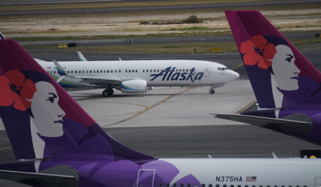 Alaska Airlines taxis to gate after landing framed by two tails of Hawaiian Airlines aircraft at Daniel Inouye International Airport.