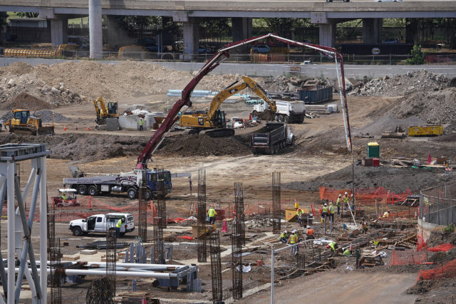 Airport Construction with workers and cement being pumped for foundations.
