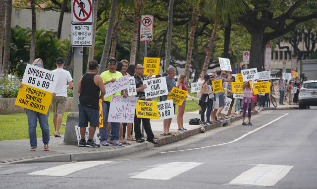 Demonstrators holding sigs in opposition to City Council bills 89 and 85 rally in front of Honolulu Hale before city council meeting.