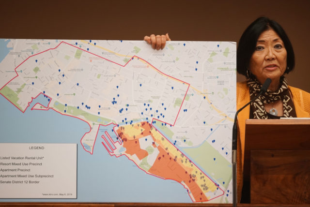 Senator Sharon Moriwaki holds a map showing some vacation rentals in her district.