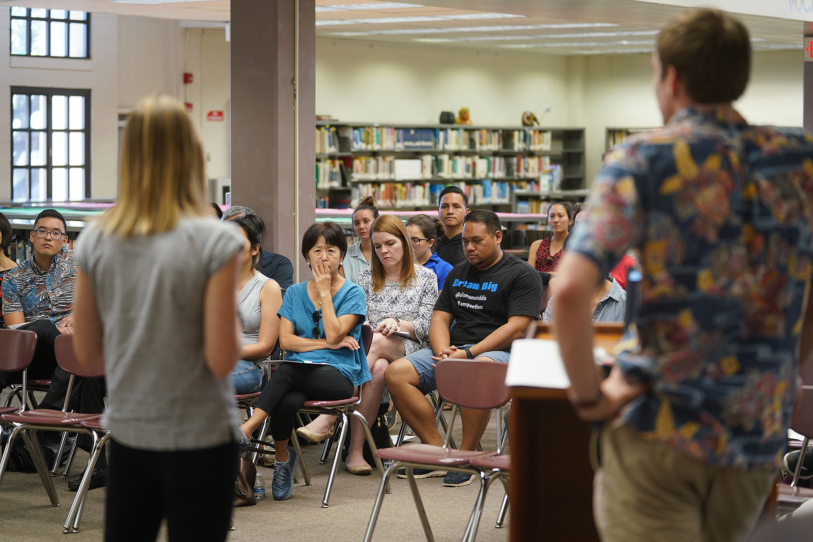 Ian Magruder from Landed with left, Alie Kelley answer questions by Oahu teachers at Farrington High School library.