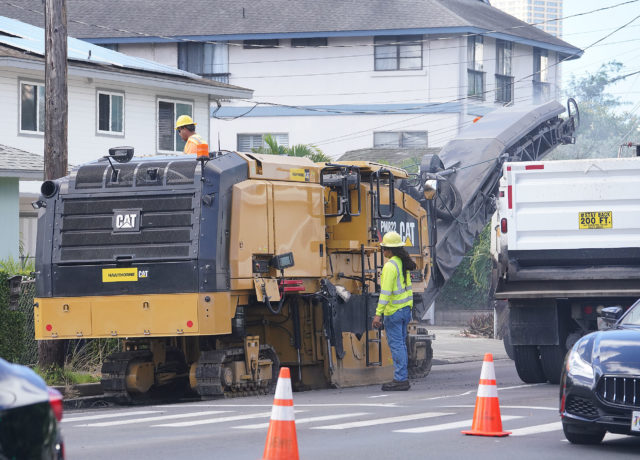 Machines remove road asphalt along McCully Street.
