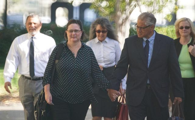 Former HPD Chief Louis Kealoha and Katherine Kealoha walk towards District Court with their legal team.