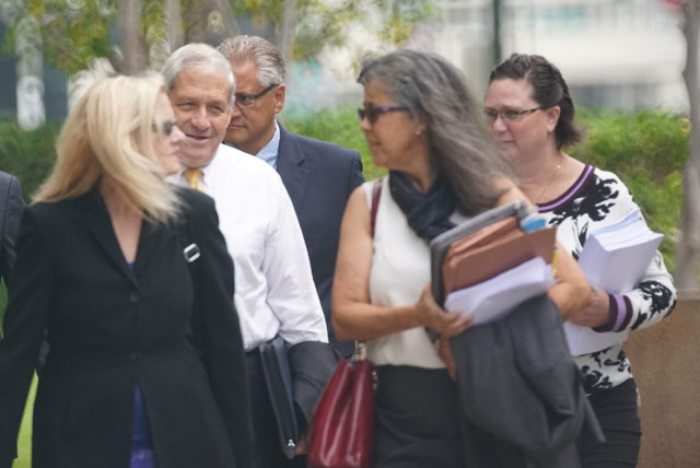 Former HPD Chief Louis Kealoha and Katherine Kealoha walk towards District Court with a new guy in white shirt.