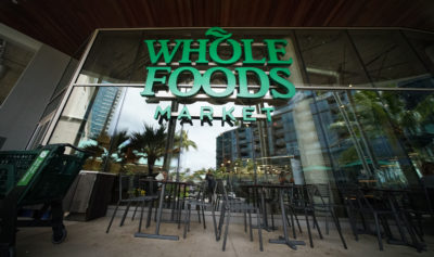 Whole Foods Kakaako with empty chairs out front with reflection of the high rises/condominiums.