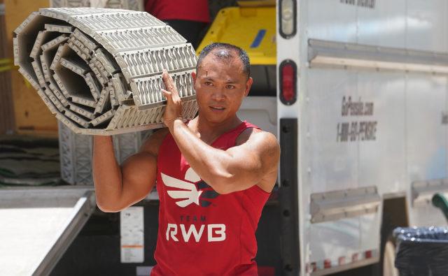 Team Red White and Blue RWB Volunteer Rolly Alvarado off loads gear at Waikiki beach .