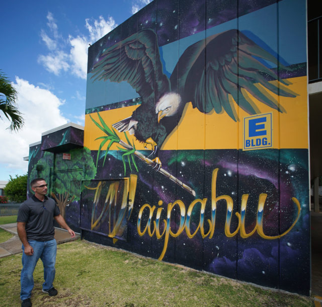 Waipahu Elementary School VP James Suster stands next to a mural painted by Waipahu artist Jesse Velasquez.