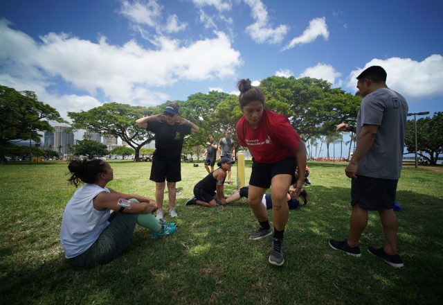 HPD Recruitment Training as left, HPD Officer Ilse Pratt talks about sit ups and how many recruits need to accomplish in a set amount of time at Magic Island.