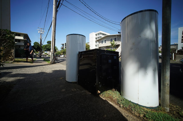 Two water heaters and a refrigerator sit on the sidewalk along Kewalo Street.