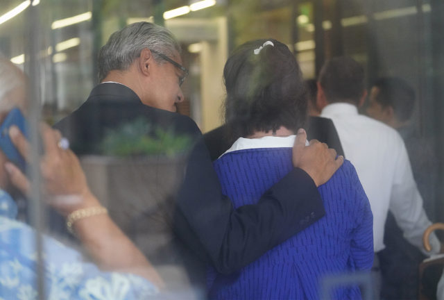 Former HPD Chief Louis Kealoha puts his arm on Katherine Kealoha while waiting in the line to go through security outside District Court.