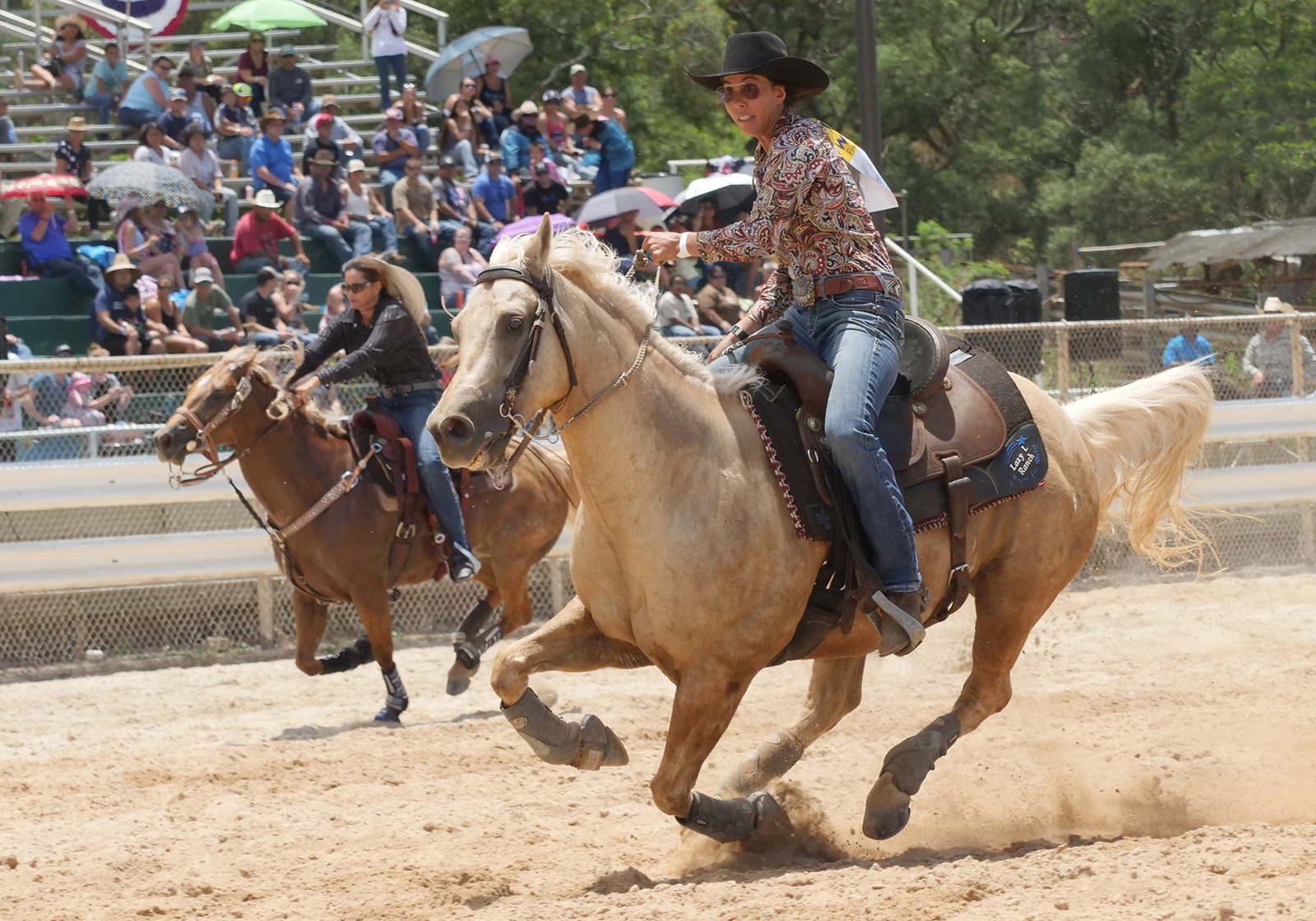 <p>Two women compete during the barrel racing event.</p>