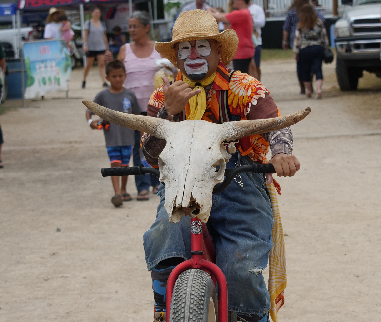 "<p>""Lil Guy"" the rodeo clown flashes a shaka as he rides his bike through the crowd to provide a little comic relief.</p>"