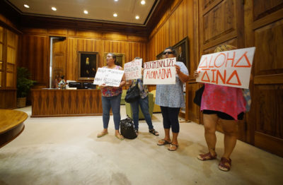 Supporters of Mauna Kea in the Governor Ige office. Left to Right, Healani Sonoda-Pale, Kamehaikana Akau, Rhonda Vincent and Kauwila Sheldon hold signs after Governor Ige announces plans for the starting of TMT construction.