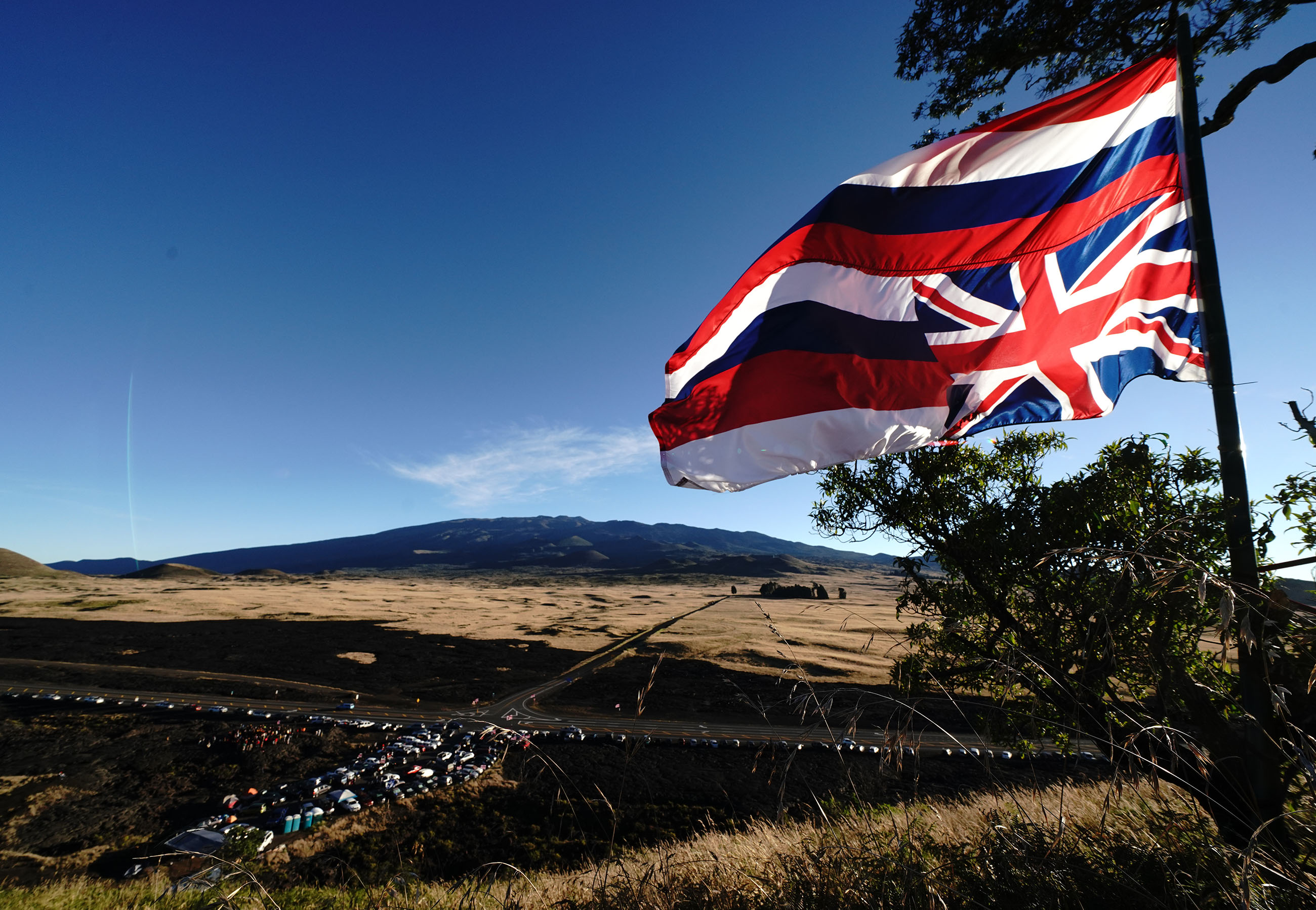 Maunakea Access Road with parked cars and people gathered along Saddle Road.