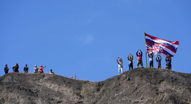 TMT Demonstrators raise a flag on the hill above the Puu Huluhulu Tree Sanctuary.