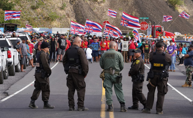 TMT demonstrators chant as State Sheriffs stand on Mauna Kea Access Road. Demonstrators were angry about a gate installed along Mauna Kea Access Road.