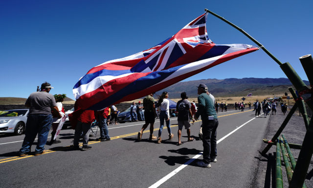 TMT Demonstrators walk up Mauna Kea Access Road with flag in foreground.