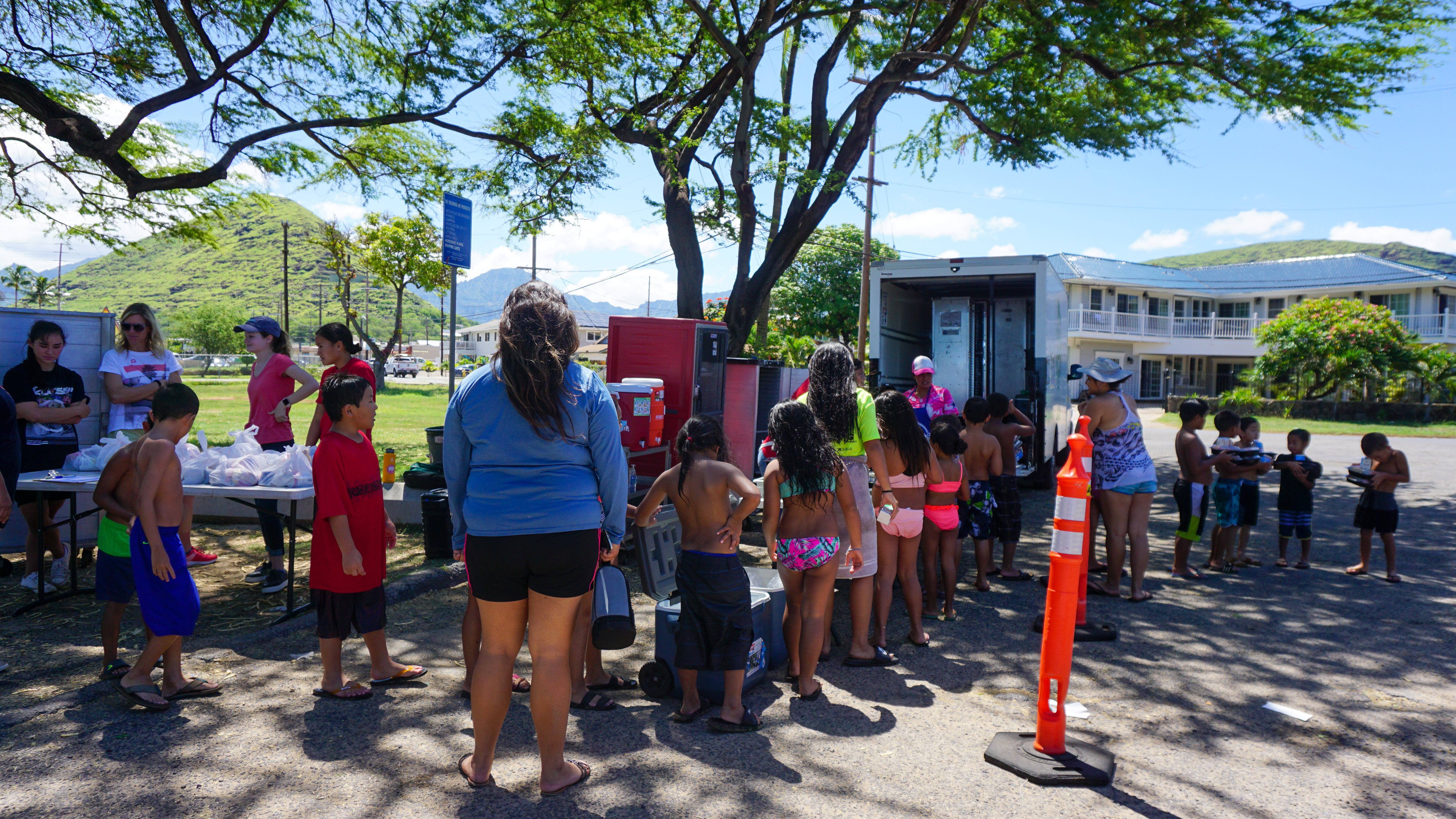 Lines of children stand in the parking lot, awaiting to pick up their free lunches from the Aina Pono truck.