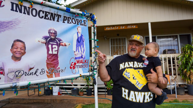 """Ed Werner points to the memorial sign of his son, Kaulana Werner. He asks his grandson, who is named after Kaulana, """"Look! You see Uncle?"""""""