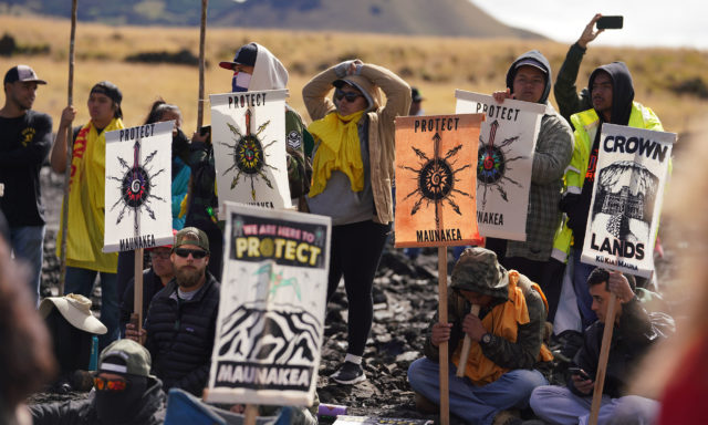 TMT Demonstrators watch as Kupuna are arrested on Mauna Kea Access Road for obstructon of government operation.