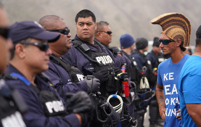 TMT protestor Kahookahi Kanuha walks past Honolulu Police Dept officers that quickly arrived on Mauna Kea Access Road. July 17, 2019