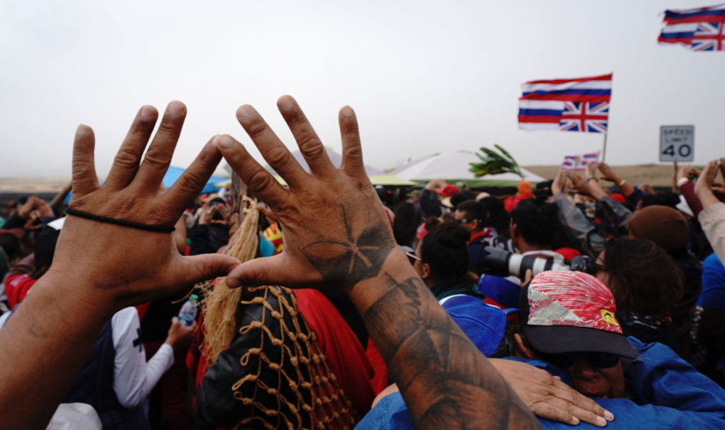 TMT Mauna Kea demonstrators hold their hands up and gesture the Mauna Kea hand symbol.