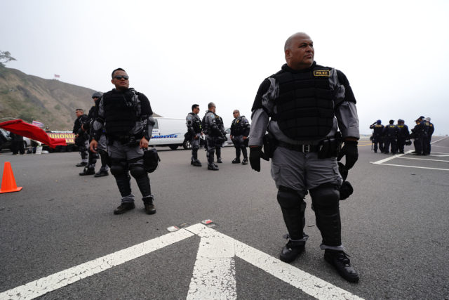 TMT Saddle Road Mauna Kea Access Road, Maui Police Dept in riot gear wait for the next shift replacing officers along the access road. July 17. 2019