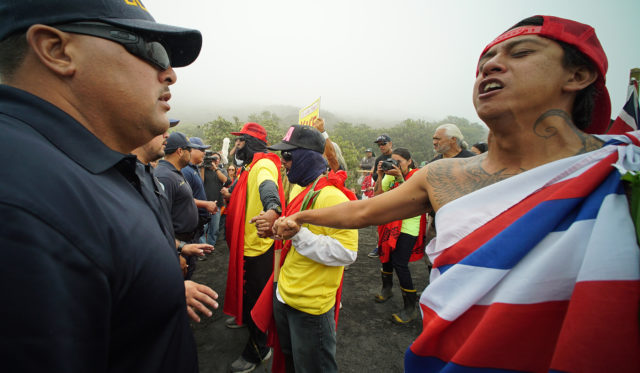 Mauna Kea supporters right hold their line as left, DLNR law enforcement officers tell them to clear the road to allow their vehicles to make the ascent to the summit. . 24 june 2015. photograph Cory Lum/Civil Beat