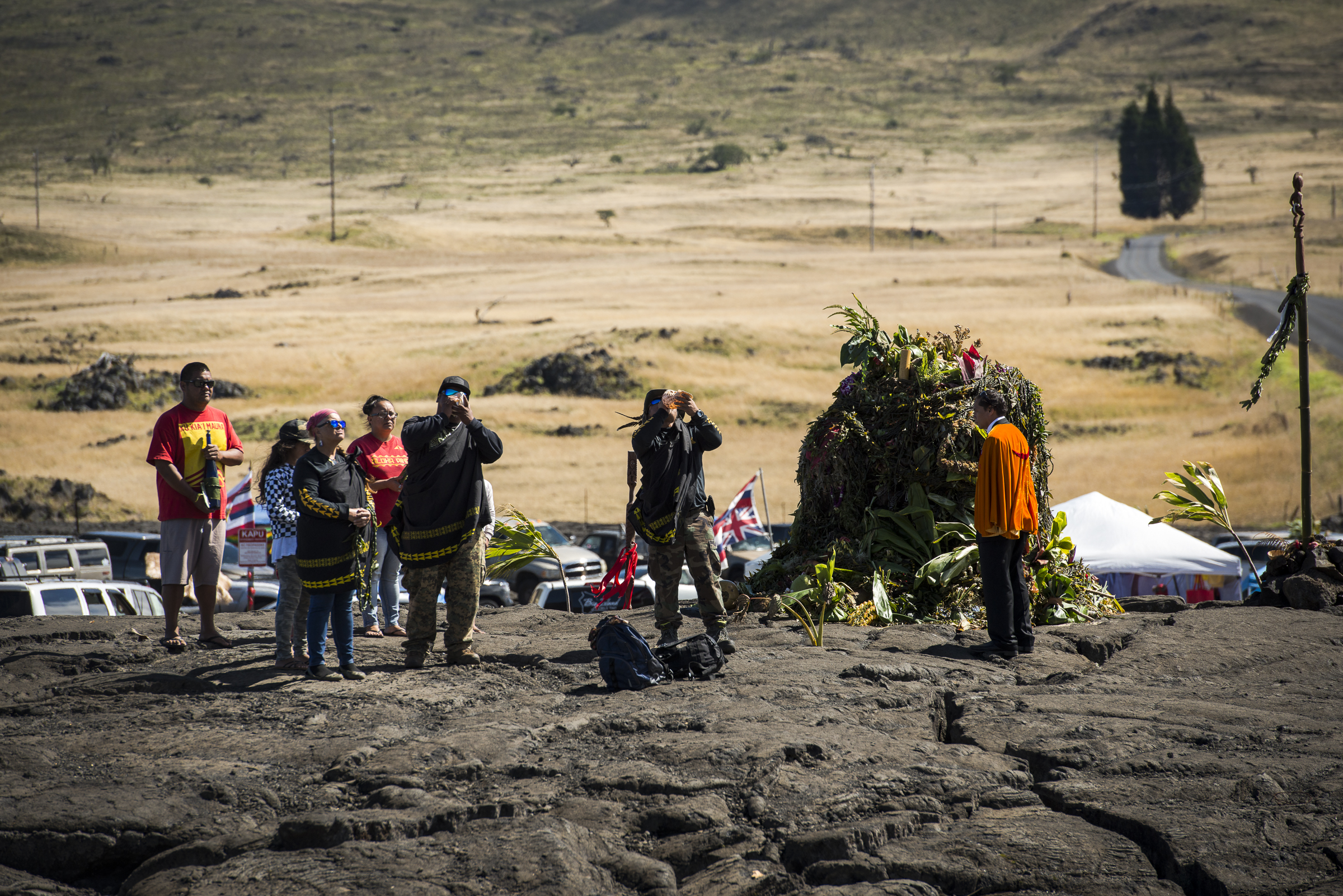 <p>Protesters blow conch shells at a kuahu (altar).</p>