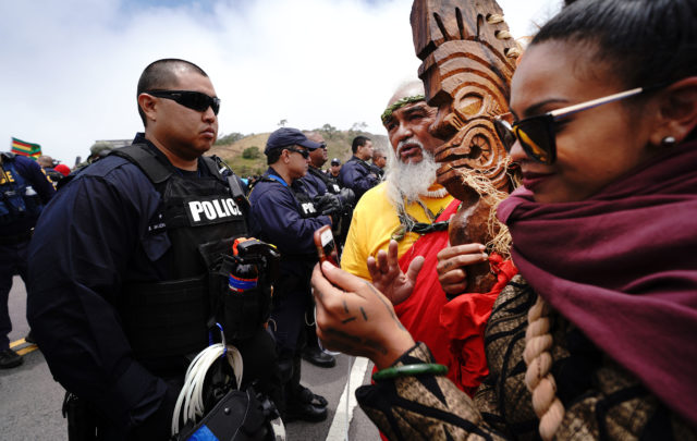 Mauna Kea TMT Demonstrators right, Hawane Rios and center, Billy Freitas stand fronting Honolulu Police Department officers along the Mauna Kea Access Road. July 17, 2019