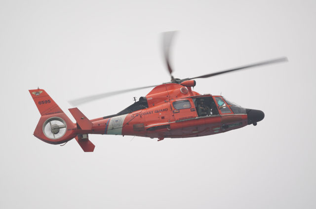 US Coast Guard helicopter cruises past Sandy Beach.