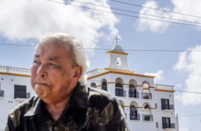 "Leo Tudela recalls his allegations of sexual abuse at age 13 by a monk at the Saint Fidelis Friary, seen in the background, in Hagatna, Guam, Thursday, May 9, 2019. Tudela was eventually moved to live in the rectory of another church where Father Louis Brouillard took interest in him. That began an eight-month period during which Tudela alleges he was regularly raped and molested. ""We're all human beings so there is always forgiveness but this person I don't think God will forgive him,"" he said. Brother Mariano Laniyo and Brouillard are now dead. Brouillard acknowledged abuse allegations before he died. (AP Photo/David Goldman)"