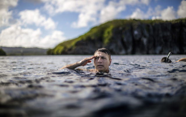 "Walter Denton Guam Sex Abuse a former Army sergeant, treads water while saluting a U.S. flag on a nearby cliff of a military base during the morning broadcast of the national anthem as he swims with his brother in Agat, Guam, Saturday, May 11, 2019. ""It helped me to stay focus every single day,"" Denton says of his time in the military and coping with a sexual abuse by a priest over 40 years ago, allegations detailed in a lawsuit. ""Every morning I looked forward to putting on my uniform and going to work. It was a distraction."" Former Archbishop of Agana, Anthony Apuron denies the allegations. (AP Photo/David Goldman)"