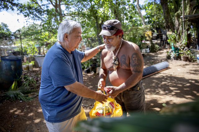 "Leo Tudela, left, brings food for Everett Torregrosa as he visits his home in Hagatna, Guam, Thursday, May 9, 2019. ""We're like brothers,"" said Torregrosa of Tudela who checks on him periodically after learning they each were victims of sexual abuse by priests when they were boys. (AP Photo/David Goldman)"