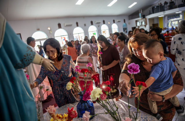 Jeanie Bamba holds her grandson, Jayce, as they lay flowers at a statue of the Virgin Mary during a Mass on Mother's Day at Immaculate Heart of Mary Catholic Church in Toto, Guam, Sunday, May 12, 2019. Nearly four centuries after the arrival of the first Jesuit missionaries, Catholicism is deeply engrained in Chamorro culture. More than 85 percent of Guam's 165,000 residents identify as Catholic. By comparison, the most Catholic city on the mainland, Boston, is 36 percent. (AP Photo/David Goldman)