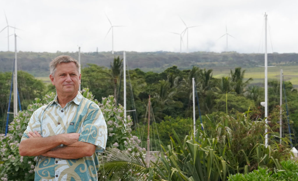 Senator Gil Riviere stands at Alii Park in Haleiwa with windmills above Waimea Bay on top of photograph.