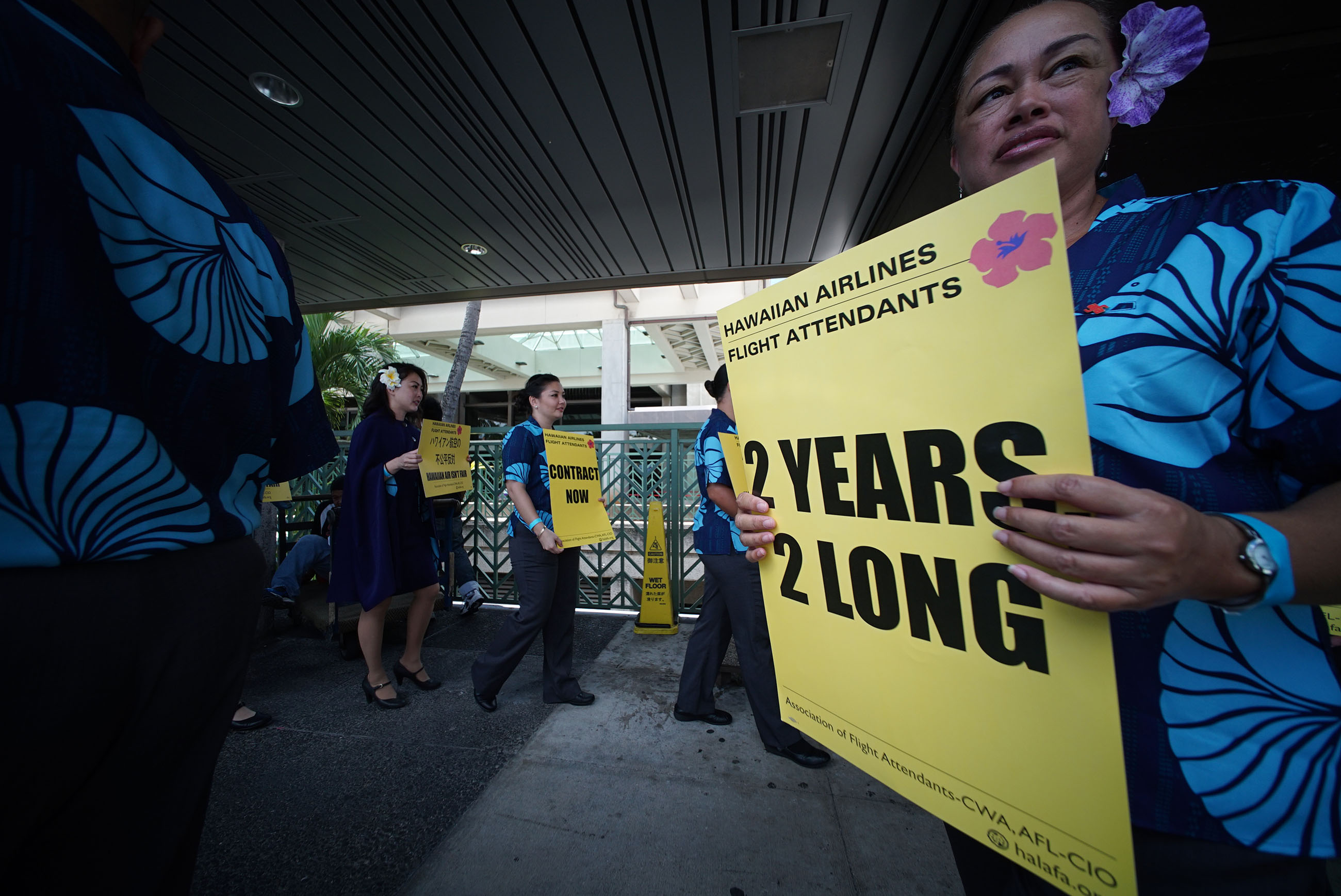 Hawaiian Airlines Flight attendants and supporters hold signs at the Daniel K Inouye International Airport.