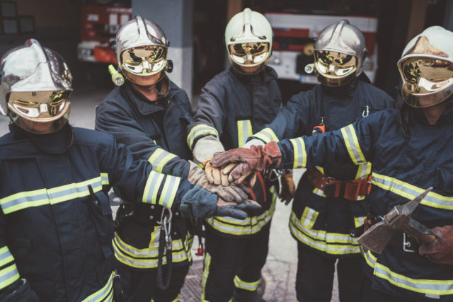 Group of firefighters dressed in fire protection suits and helmets ready for work