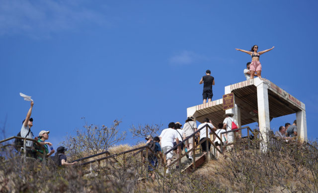 Visitors disregard 'Keep Off' signs and stand on top the Diamond Head Summit lookout bunker.