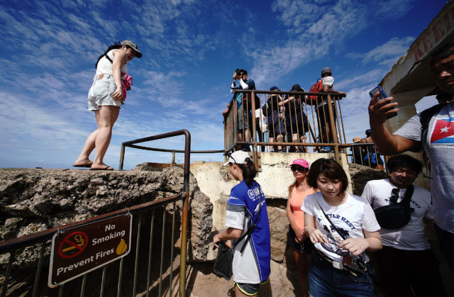 Visitors at the Diamond Head summit lookout enjoy views on a beautiful day.