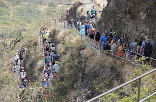 Scores of hikers ascend the trail to the summit of Diamond Head. The trail snakes towards the entrance of the tunnel near the summit.