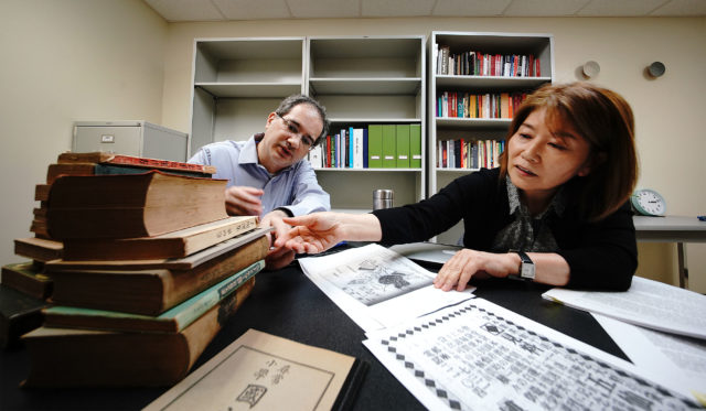 Dr. Andrew Wertheimer PhD and Dr. Noriko Asato, PhD both UH Library professors with some copies of old Hakubundo Japanese bookstore advertisements they found through their research.